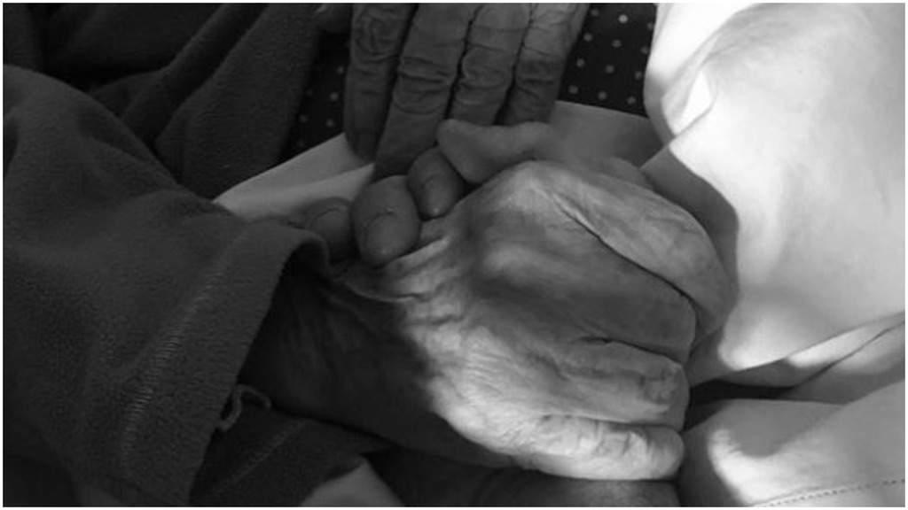 La mano di Luca Vismara tiene stretta quella della nonna sul letto in una immagine in bianco e nero