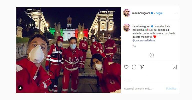 Foto di Raoul Bova e Rocio Monuz Morales insieme a dei volontari della Croce Rossa sulle scale del Campidoglio di Roma, con lo sfondo illuminato con i colori della bandiera dell'Italia