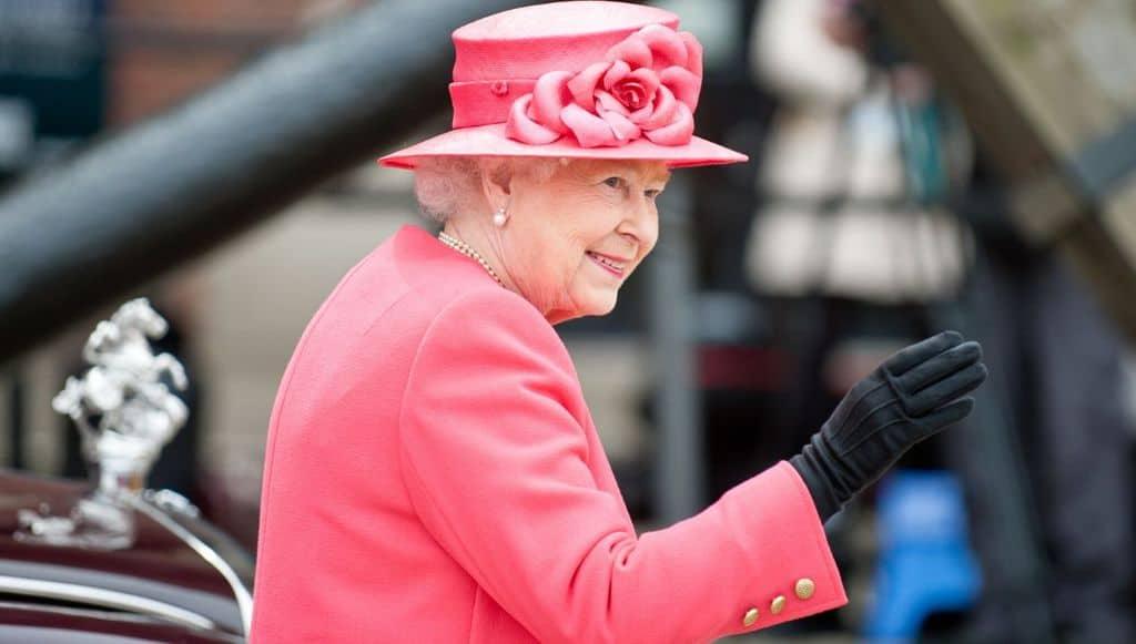 La regina Elisabetta vestita di rosa e sorridente che saluta i sudditi