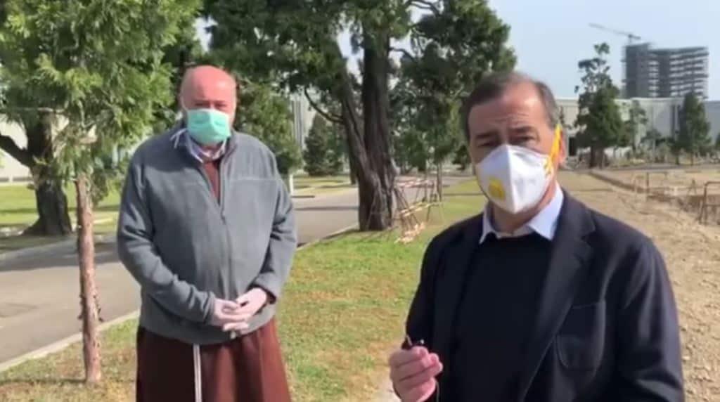 Beppe Sala con la mascherina e il microfono in mano di fronte al cimitero di Milano. Alla sua destra, leggermente indietro, anche un parroco