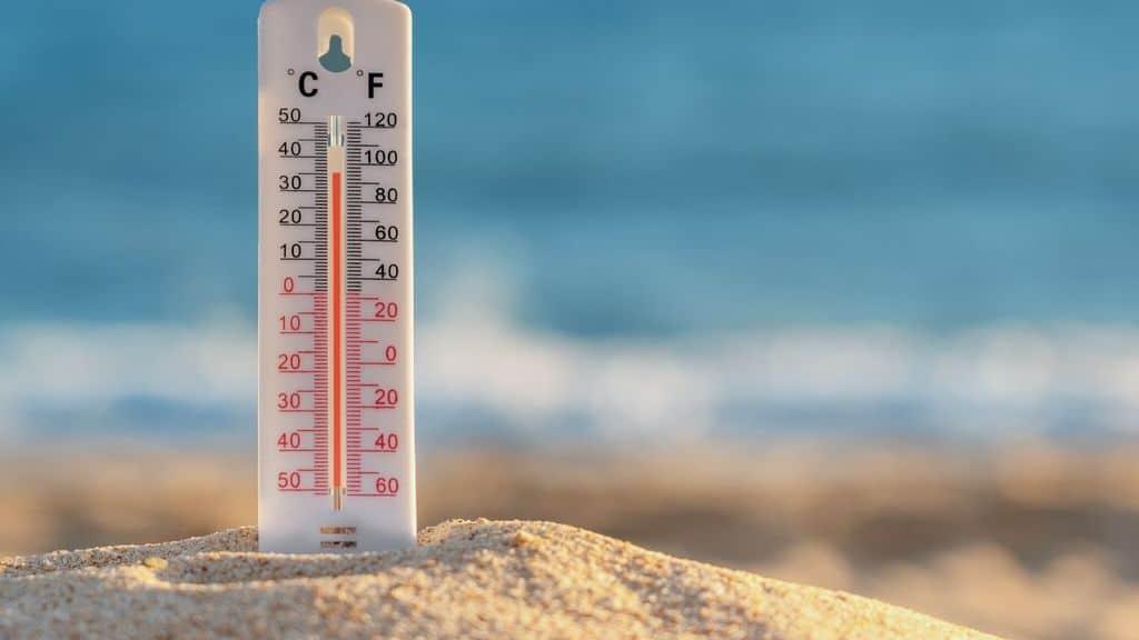 Un termometro nella sabbia in spiaggia