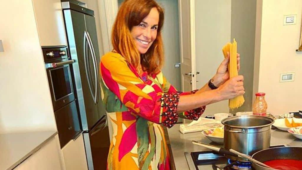 Cristina Parodi nella sua cucina con degli spaghetti in mano sospesi sopra la pentola