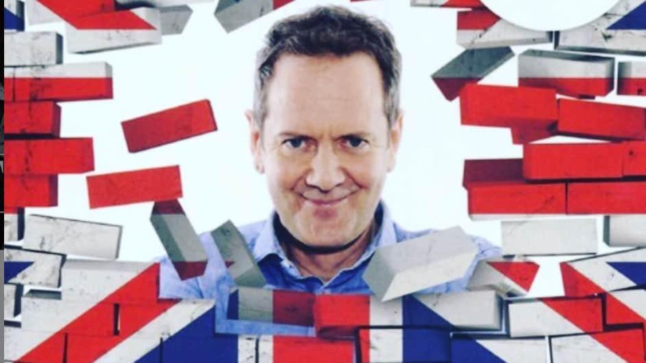 John Peter Sloan che sbuca con la sua faccia da un muro con disegnata la bandiera inglese, rompendolo