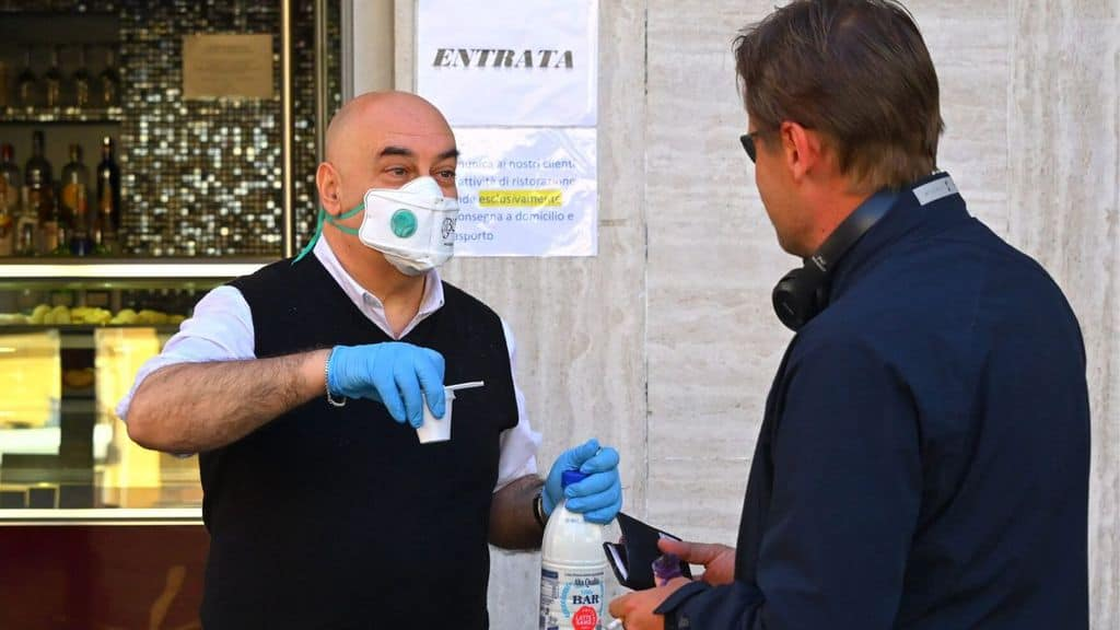 Un barista serve un caffè con indosso una mascherina per il Coronavirus