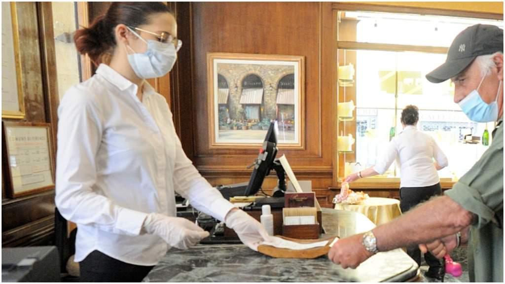 una barista alla cassa con mascherina e guanti che passa una ricevuta a un cliente, con la mascherina e il cappellino