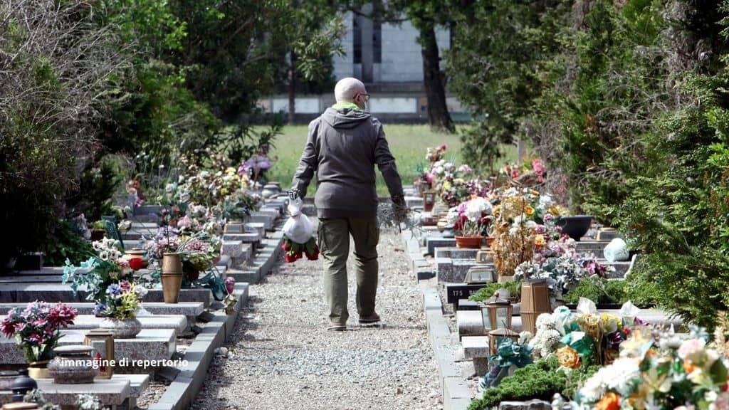 un uomo che cammina dentro un cimitero