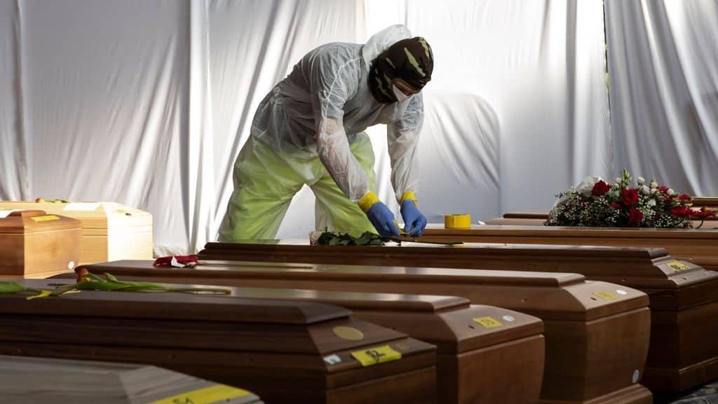 Un soldato con mascherina sulle bare dei morti da Coronavirus