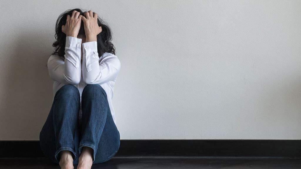 una donna disperata con le mani in faccia seduta per terra