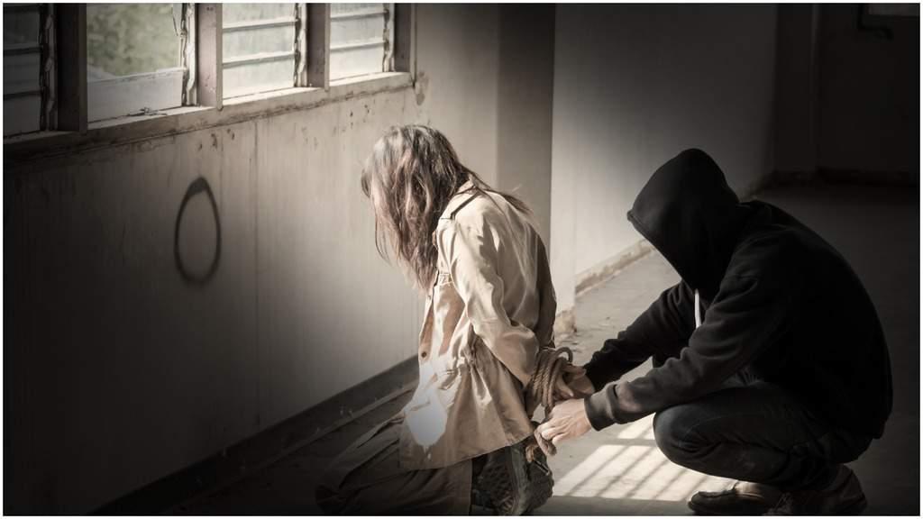 donna inginocchiata per terra di profilo mentre una persona incappucciata armeggia con delle corde intorno alle mani della donna