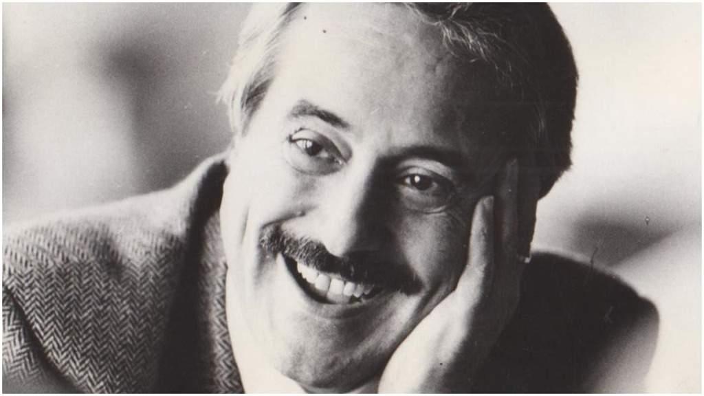 Giovanni Falcone sorridente con il volto appoggiato su una mano
