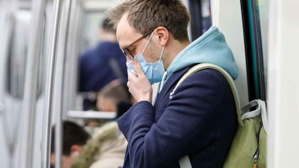 Un uomo con mascherina in metropolitana