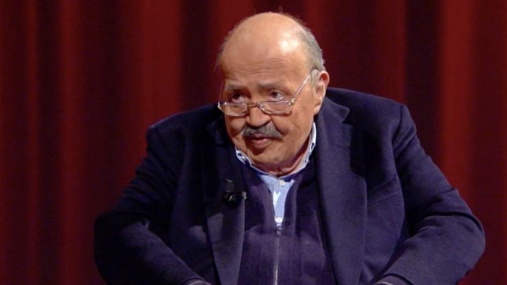 Foto di Maurizio Costanzo sulla poltrona dello studio della trasmissione L'intervista con sfondo rosso