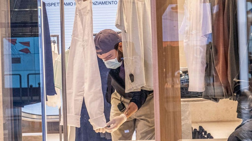 un commesso cura la vetrina di un negozio
