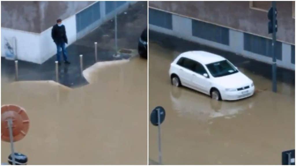 una persona su un marciapiede accerchiata dall'acqua in strada e una macchina con l'acqua altezza gomme