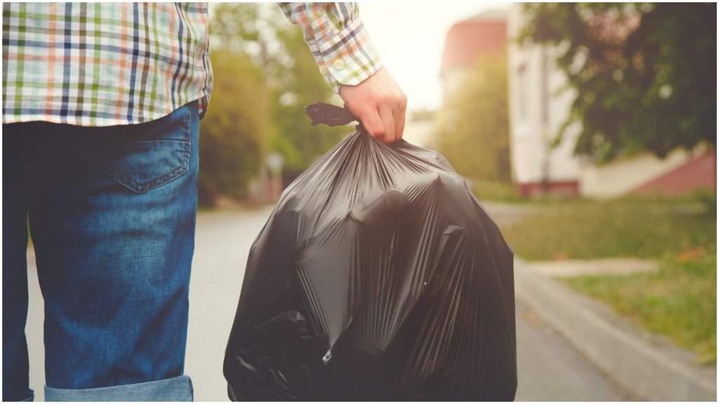uomo con in mano un sacco della spazzatura