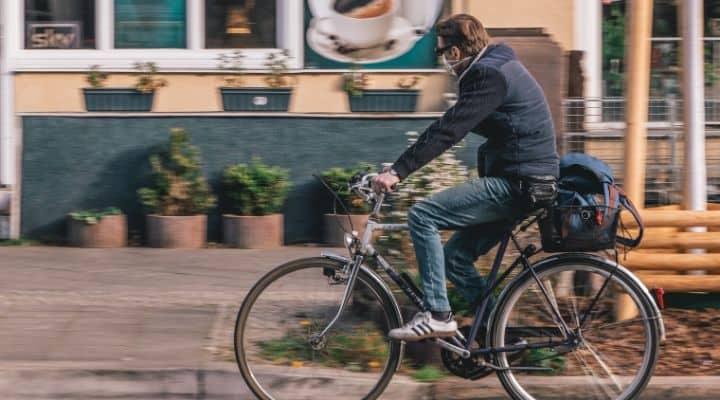Un uomo che va in bicicletta. Sullo sfondo una casa e alcuni vasi di fiori davanti alla facciata