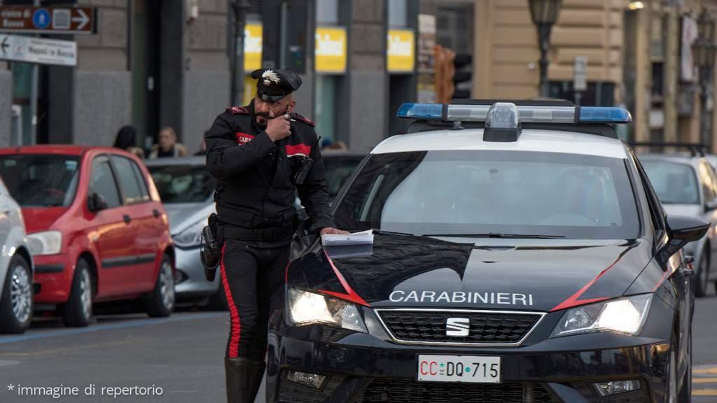 auto dei carabinieri in città con un carabiniere di fianco
