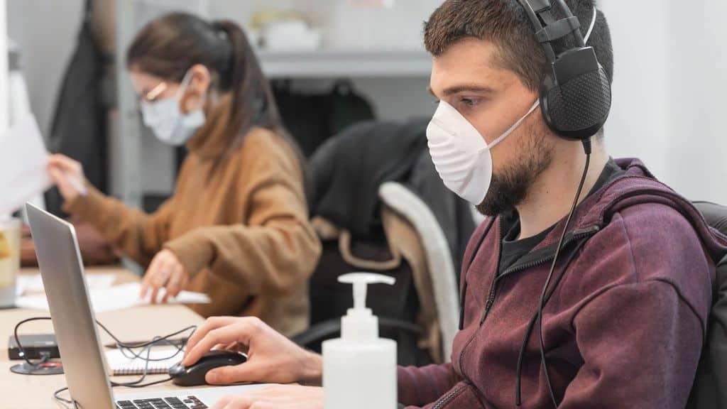 Impiegato al lavoro con mascherina per il Coronavirus