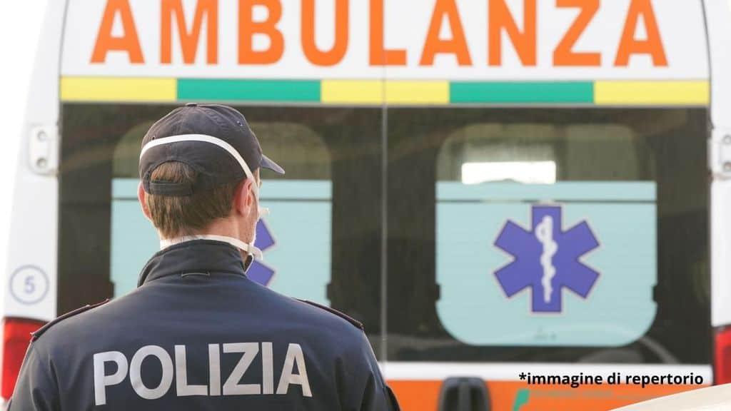 Un poliziotto di fronte a un ambulanza