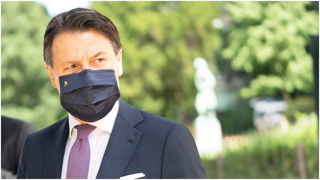 Giuseppe Conte con la mascherina nera con una piccola bandiera italiana