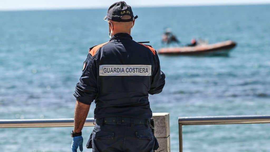 membro della guardia costiera guarda il mare dalla spiaggia