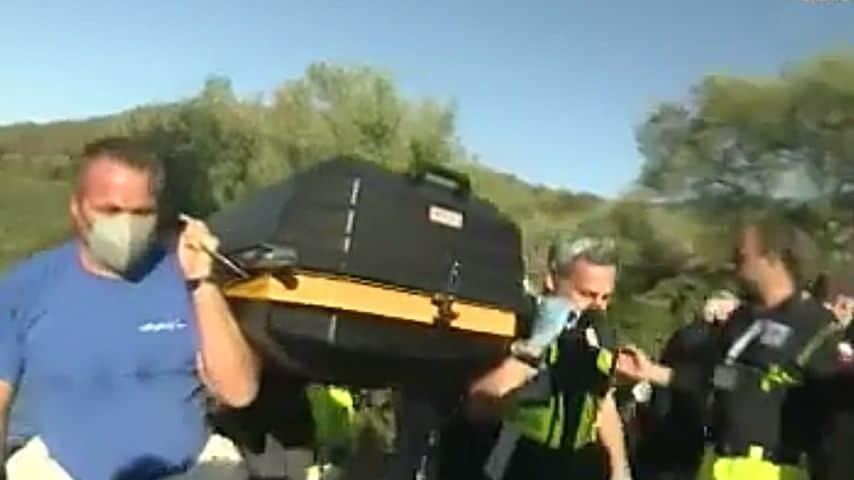 I soccorsi portano via la bara con i resti