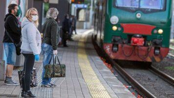 persone prendono il treno con le mascherine
