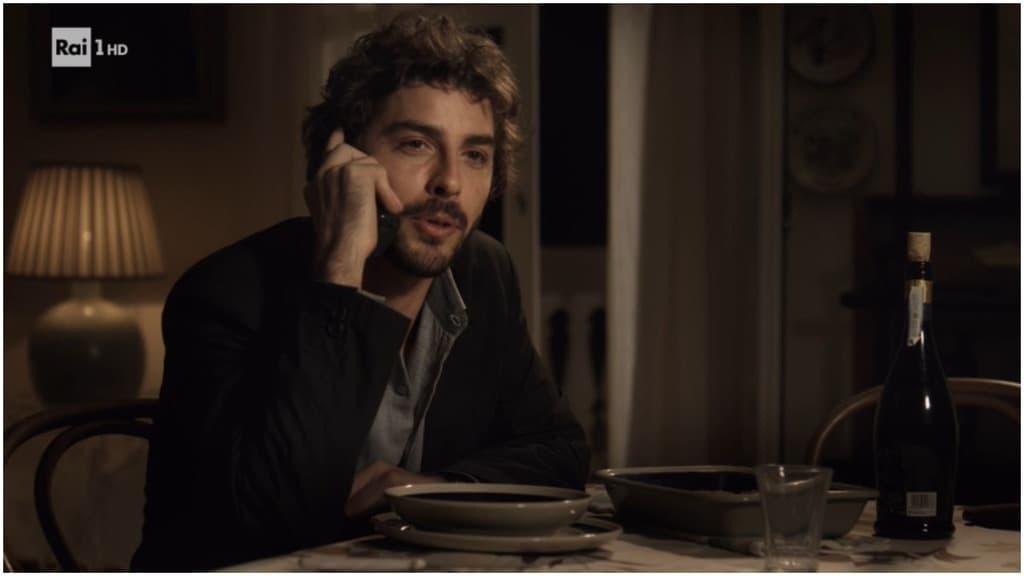 Il giovane Montalbano, seduto a tavola, al telefono