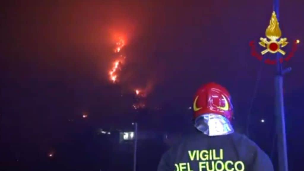 Vigile del fuoco di spalle guarda l'incendio ad Altofonte