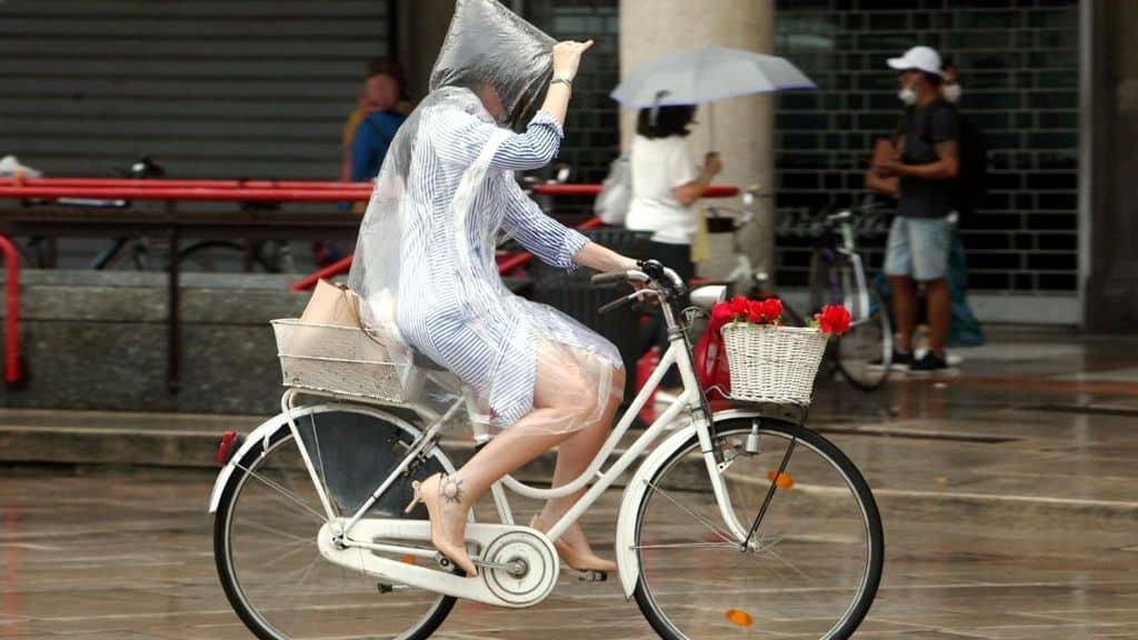 donna in bicicletta sotto la pioggia