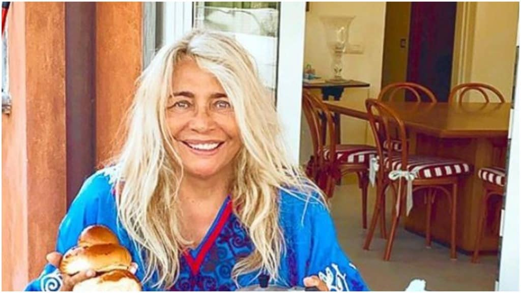 Mara Venier sorridente e seduta a tavola
