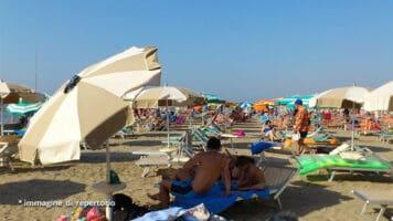 persone sotto gli ombrelloni in spiaggia