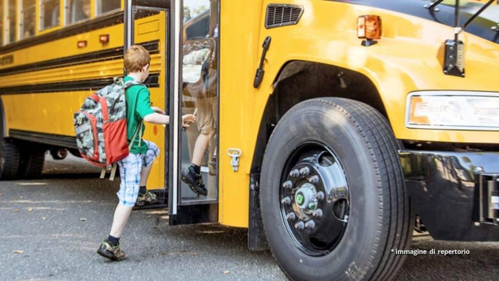Un bambino sta salendo sullo scuolabus
