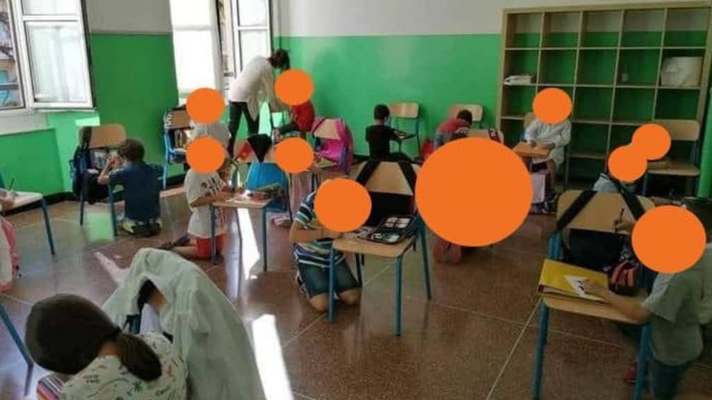 genova bambini seduti per terra a scuola