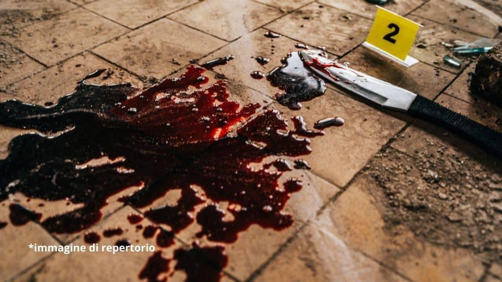 coltello sporco di sangue per terra