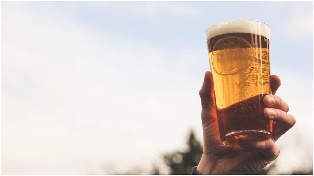 mano di uomo che tiene in mano un bicchiere di birra