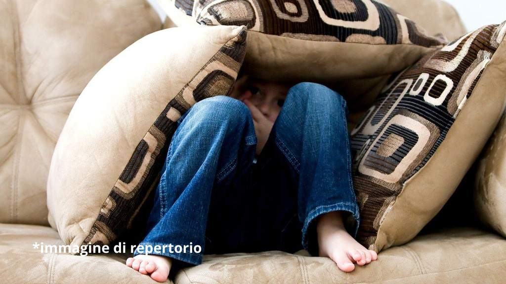 bambino triste su un divano