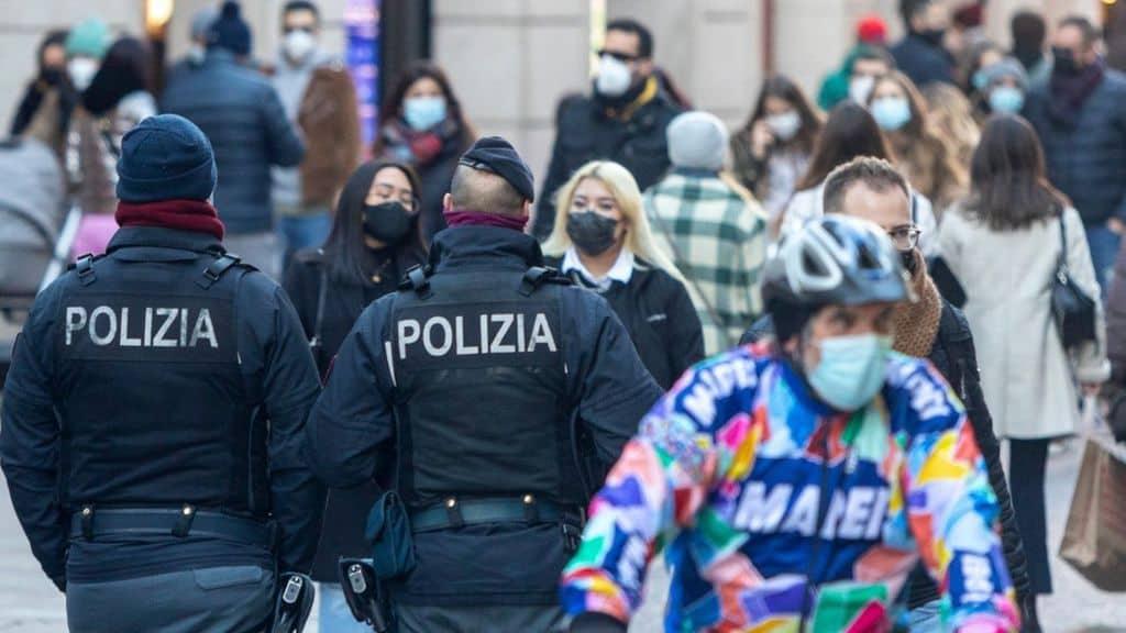 persone a passeggio in città con la mascherina e la polizia