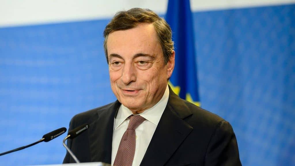 Mario Draghi di fronte a un microfono, su sfondo bianco e bliu