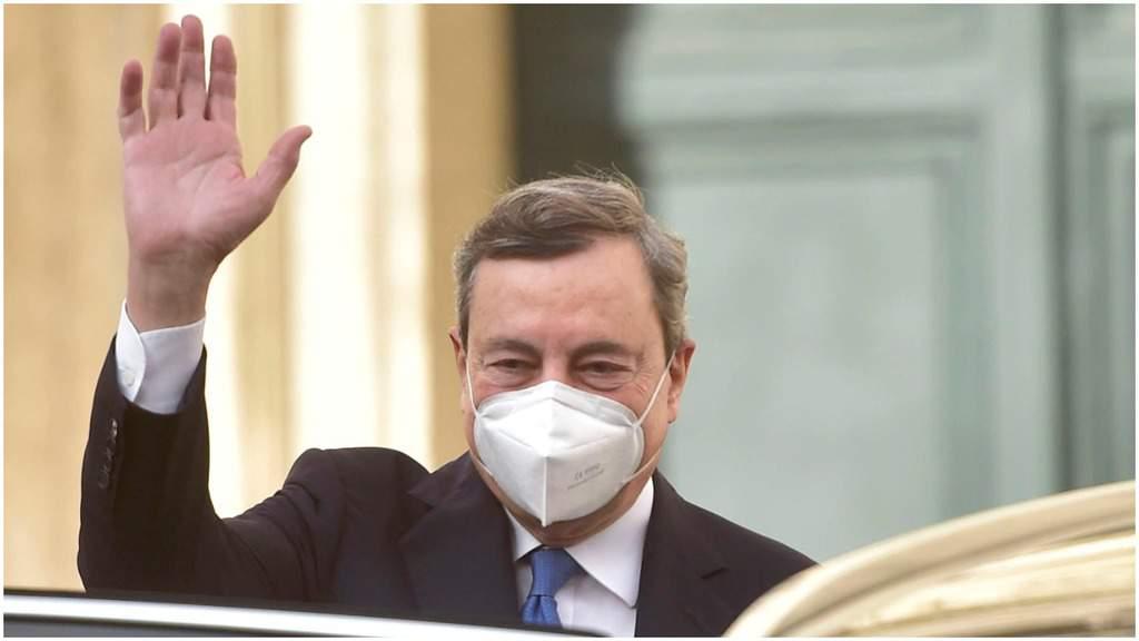 Mario Draghi, con la mano destra alzata in segno di saluto e la mascherina sul volto
