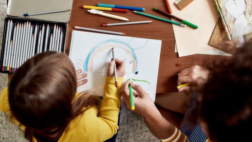 baby sitter e bambino colorano insieme